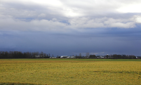 western state: Dark, ominous, winter rain clouds spread over the countryside in western Washington State. Stock Photo