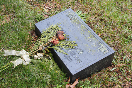 Faded flowers lay on a grave headstone.