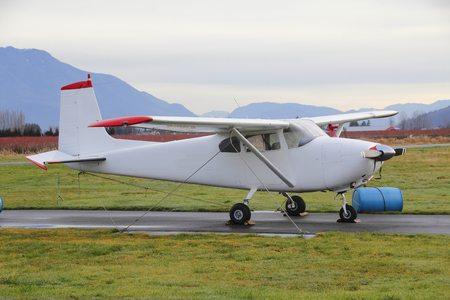 small plane: Barrels, wires, cables and ground bolts are used to secure a small plane while parked. Stock Photo