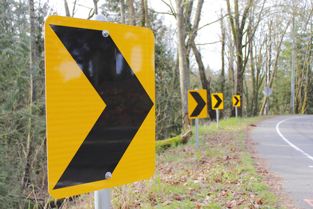 Signs with distinctive arrows indicate a sharp curve or bend in the road. Imagens
