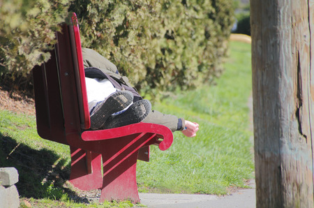 homeless person: A homeless person sleeps on a park bench. Stock Photo