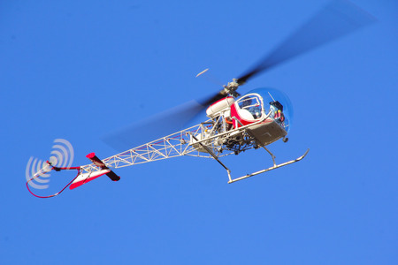seater: A small two seater helicopter hovers overhead against a clear blue sky.