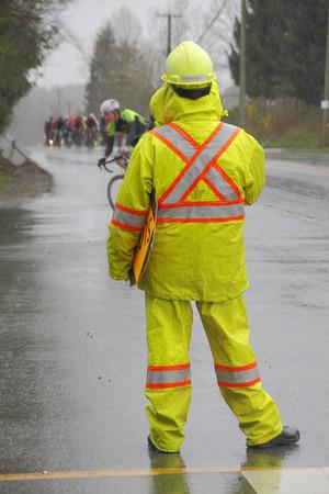 Een verkeersleider horloges voor voertuigen tijdens een wielerwedstrijd Stockfoto