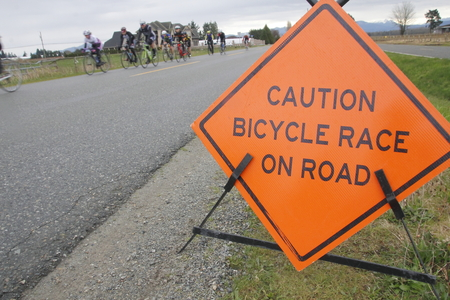 signage outdoor: A sign is used to inform motorists that a bicycle race is underway.