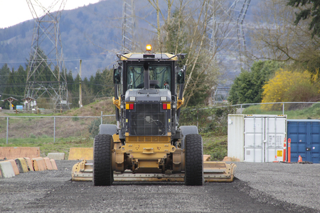 grader: A Grader is used to level dirt on a parking area. Stock Photo