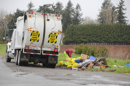 civic: A civic worker collects garbage in a rural area in southern BC, Canada on March 24, 2016. Stock Photo