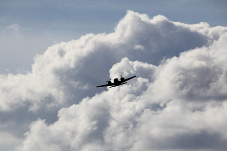 billowing: A turboprop plane emerges out of billowing cumulus clouds. Stock Photo