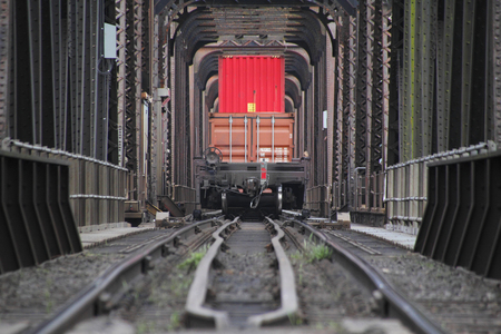 steel girder: Cargo is stacked on a train car as it passes across an old, steel and girder bridge.