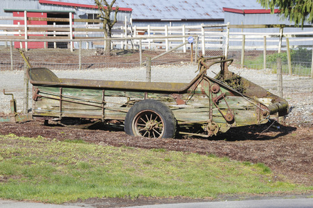 spoked: Old farm equipment from the turn of the century stands outside of a farm.