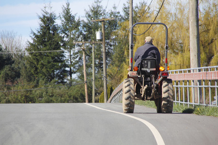 bike lane: A farmer uses the bike lane to drive his utility tractor on a public road. Stock Photo
