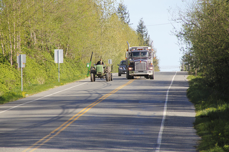 slow lane: A large dump truck passes a farm tractor on a two lane road. Stock Photo