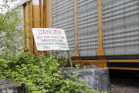 canadian pacific: A train rushes past a sign erected by Canadian Pacific warning of the danger. Stock Photo
