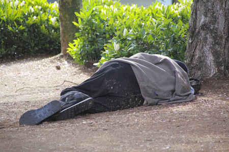 destitute: Alone and destitute, a homeless man finds sleep in a hidden place.