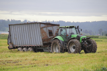 tred: A tractor is often used in many ways and in this case its used for hauling a metal shed.
