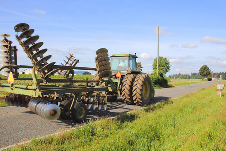 single lane road: A Washington farmer drives his tractor while transporting his plow on a rural road. Stock Photo