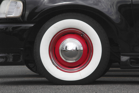 hubcap: Close on Whitewall tires with red trim and a silver, reflective hubcap.