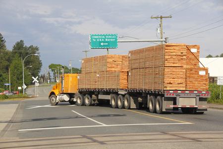 이중 평판화물 트럭이 미국의 국경으로 이동하여 캐나다 목재 제품을 배달합니다. 스톡 콘텐츠