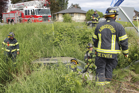 Fire and Rescue Services rescue a driver after his vehicle was hit by a truck at Townshipline and Riverside Road in Abbotsford, BC on May 11, 2016. 新聞圖片