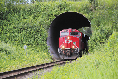 canadian pacific: A Canadian Pacific train emerges out of a short tunnel beneath a road on May 10, 2016.