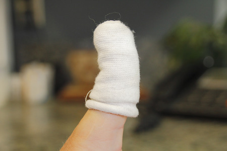 specifically: A badly cut thumb has been treated with a special bandage made specifically for injured digits.