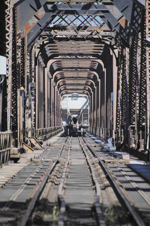passing over: A vertical view of a train passing over an old steel rail bridge.