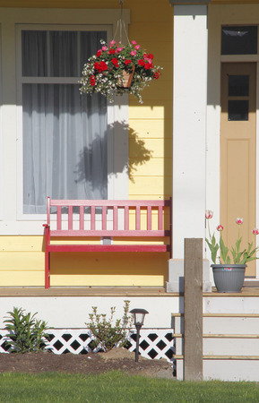 hanging basket: A hanging basket and bench on a neat and prim porch conveys traditional Americana. Stock Photo