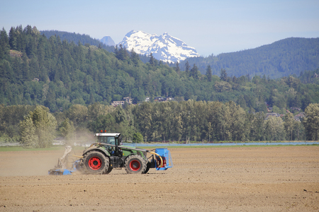 snow capped mountain: A tractor plows his field with a snow capped mountain in the background.