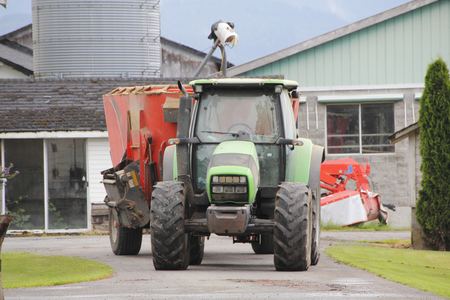 auger: A tractor transports an auger mixer, used for mixing feed for livestock.