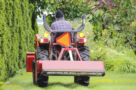 A farmer drives a small utility tractor.