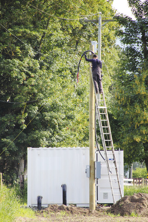 telephone pole: A telephone pole is being re-positioned with new cables added. Stock Photo
