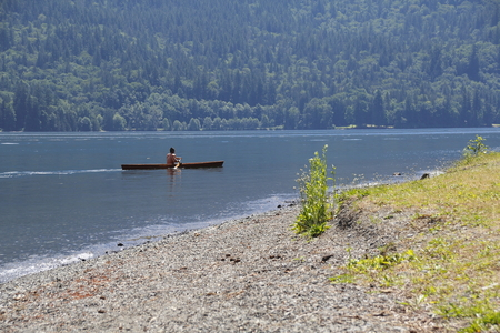canoeist: A canoeist in a traditional wooden canoe, paddles near a lake shoreline.