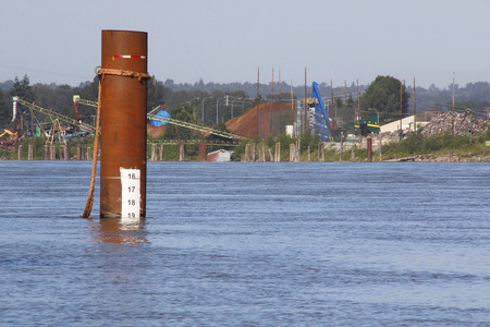 A marker on a post indicates river water levels are getting dangerously high.