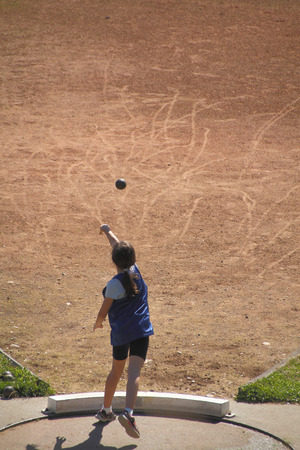 high angle: A high angle view of a young athlete throwing a shotput into the pit. Stock Photo