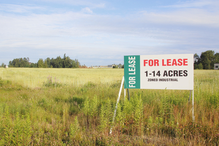 advertises: A sign advertises land acreages for lease.