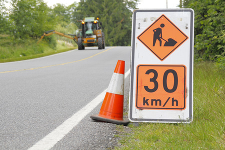 be aware: A sign warns oncoming traffic that a working crew is up ahead. Stock Photo