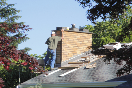 A man works on the roof of his house repairing and updating. Archivio Fotografico