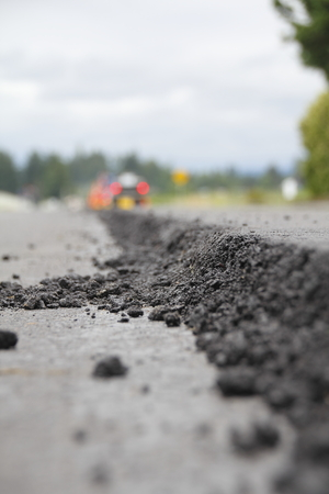 A thick layer of asphalt is applied to upgrade a road surface.
