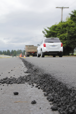 seepage: A thick layer of asphalt is applied to upgrade a road surface.
