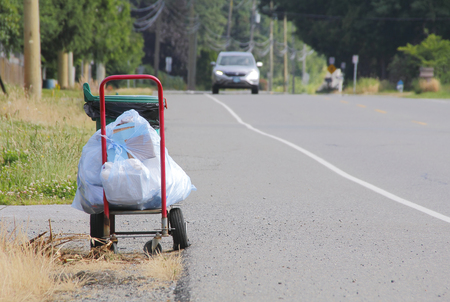 specific: Garbage is placed roadside for pickup during specific days of the week.
