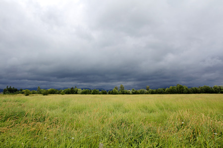wide  wet: Dark clouds, heavy with rain, stretch across the plains. Stock Photo
