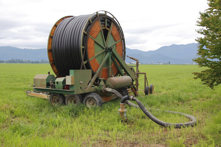 well water: An irrigation hose and reel are connected to a control valve tapping into underground well water.