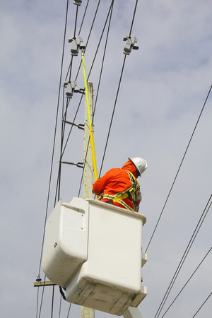 linesman: A linesman uses a rod to retrieve a current sensor reader used to measure voltage passing through hydro electric wires.
