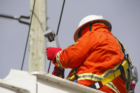 linesman: A linesman checks data on a wireless voltage reader used to gauge current through electric lines.