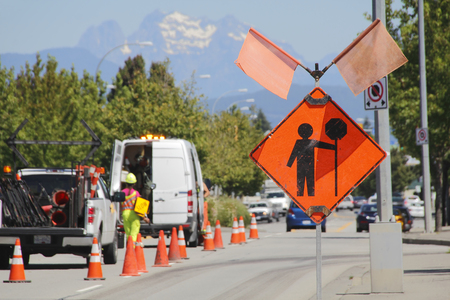 ensure: Cones, signs and a traffic controller are used to ensure safety on a road construction site.