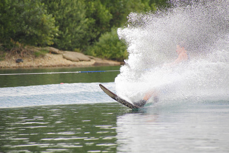 water spray: Water skis cut across the lake causing a wall of spray.