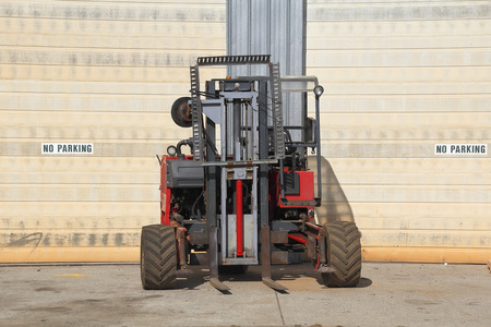 A small industrial forklift parked outside a warehouse.