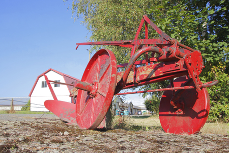 A decorative antique red plow from the early 20th century. Stock Photo