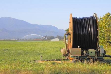 acres: A large spool of industrial sized hose is long enough to water acres of crop.