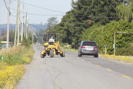 slow lane: A van passes a farm vehicle on a country road.