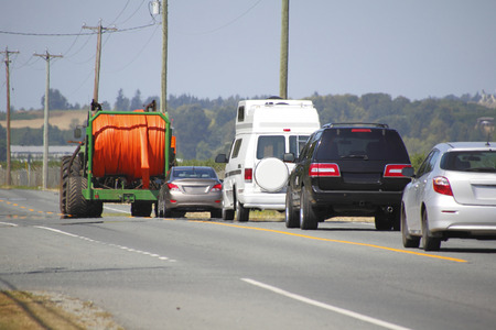 Slow moving farm machinery obstructs visibility and generates frustrated motorists.